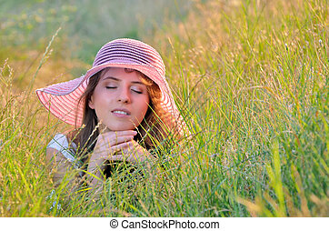 girl lies among the wild flowers in summer time