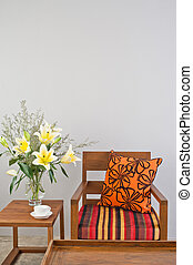 Colorful upholstered chair with side table and flowers