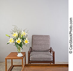 Beige upholstered chair with side table and flowers