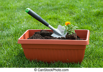 Gardening - Garden shovel and a flower in a pot with compost