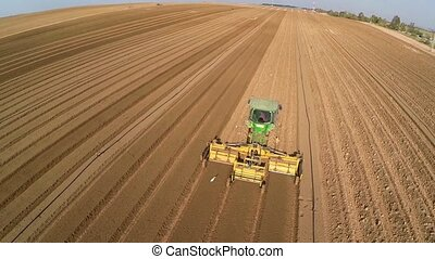 Tractor works on the Potato field - Beautiful Aerial view of...