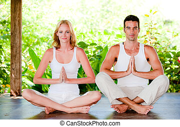 Couples Yoga - An attractive couple practicing yoga outdoors