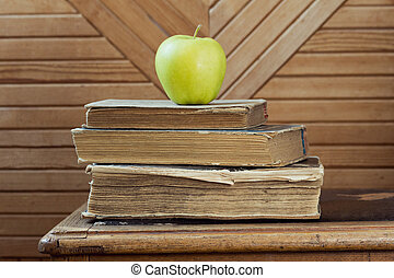 Stack of old books and green apple  on old chair