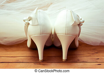 Wedding shoes and veil. White wedding shoes and veil on the...