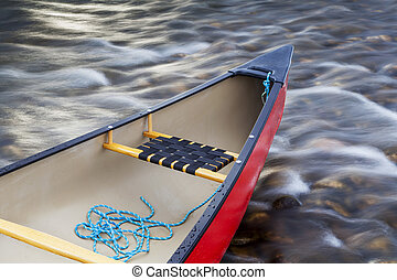 red canoe stern with a rope against river rapid