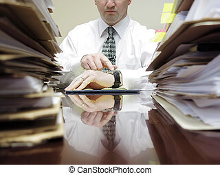Businessman at Desk with Files Pointing at Watch -...