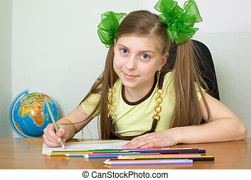 Girl sitting at a table with pencils - The girl sitting at a...