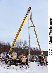 Construction of power lines using a mobile crane in a winter...