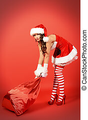 heavy bag - Beautiful young woman in Santa Claus costume...