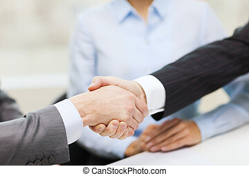 two businessmen shaking hands in office - businesss and...