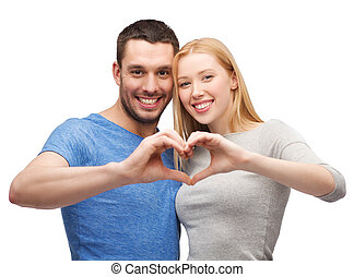 smiling couple showing heart with hands - love and family...