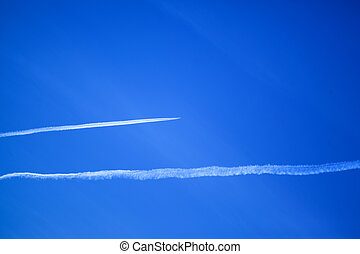 two horizontal jet trails and a deep blue sky