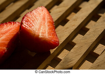 two strawberries on backing of wood in the sun