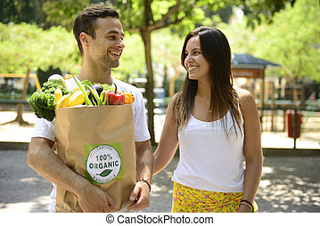 Couple with bag organic vegetables - Happy couple carrying a...