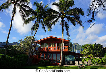 Red Two Story Beach House with tall coconut trees and...