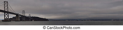 Panoramic of Boat sail by the San Francisco Bay Bridge on a foggy day with Oakland Harbor in the Background.