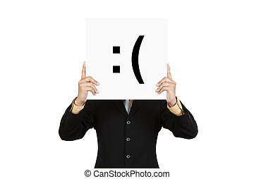 Businessman hold board with sad face emoticon isolated on...