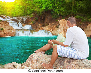 Couple near waterfall on sunrise time