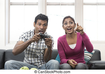 Indian Couple Having Fun Playing Video Console Game