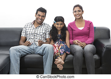 Parents and child relaxing at home on sofa.