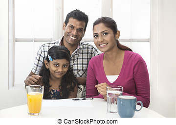 Indian family helping their child with her study work -...
