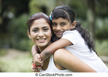Happy Indian mum and her child playing outdoors - Happy...