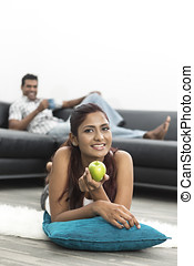 Happy young Indian woman relaxing at home
