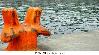 Orange bollard on a quay by the water