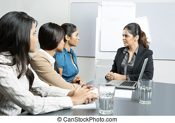 Serious boss talking with her team. - Indian business woman...