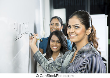 Business leader writing on whiteboard - Indian business...
