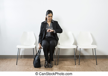 Indian woman waiting for interview & checking time.