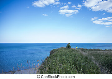 Man Sitting on Precipice Cliff Edge, overlooking the clear...