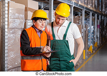 Manager and worker in warehouse - Female manager giving...