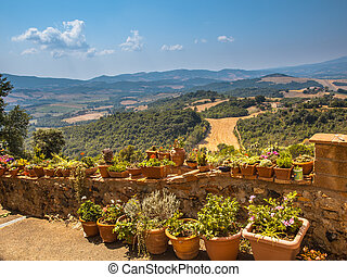 View over Tuscany Hilly Landscape with Pots of Flowers along...