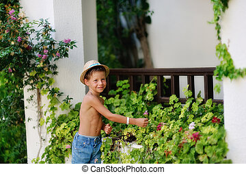 little gardener - little boy in shorts and straw hat in a...