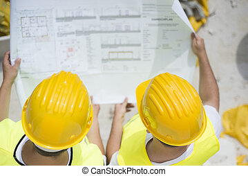 Engineer builders in safety vest with blueprint at...