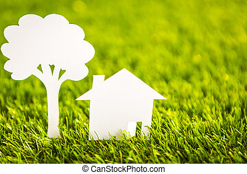 Paper cut of house and tree on fresh spring green grass -...