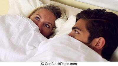 Cute couple hiding under the sheets at home in bedroom