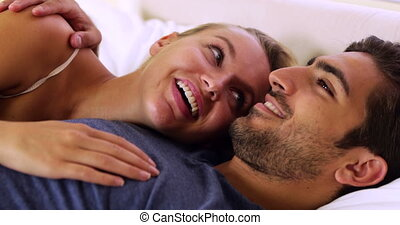 Cute couple chatting and cuddling in bed at home in bedroom