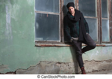 young fashion man leans on window sill - young fashion man...