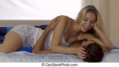 Young couple chatting and cuddling in bed at home in bedroom