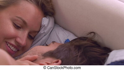 Intimate couple talking in bed at home in bedroom