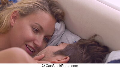 Intimate couple chatting in bed at home in bedroom