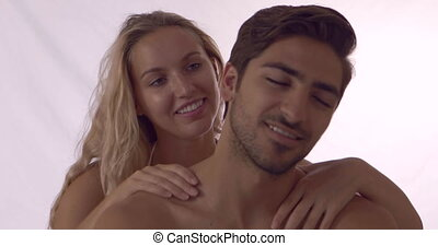Blonde girl giving her boyfriend a shoulder rub at home in...