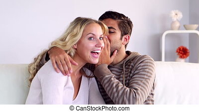 Man whispering a secret to his girlfriend on the couch at...