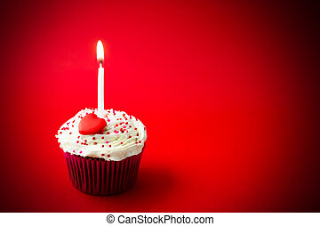 sweet little birthday cake with candles, red background