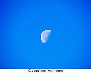 Bright half moon in the sky of noon