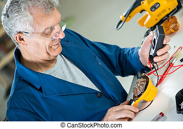 Testing Voltage - Senior adult Electrician using Digital...