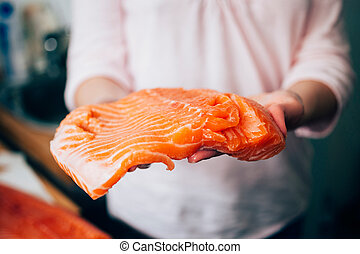 Raw salmon in woman hands - Woman holding fresh piece of...