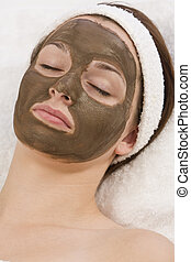 Chocolate Face Mask - A beautiful young brunette woman rests...